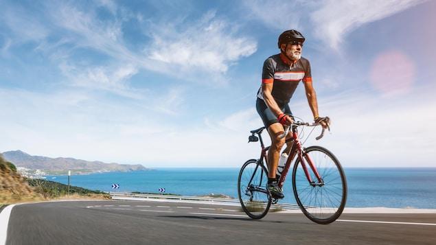 Un cycliste monte une côte à vélo.