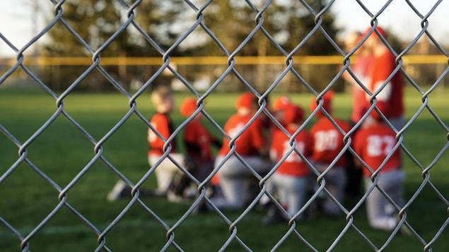 Des jeunes agenouillés sur le terrain de baseball regardent leurs entraîneurs.