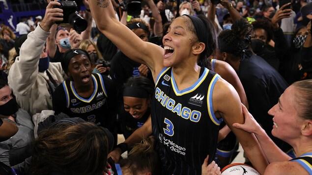 La basketteuse Candace Parker, entourée de ses coéquipières et de la foule, lève le bras dans les airs et affiche un large sourire en guise de célébration.