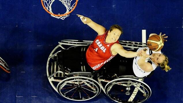 La joueuse canadienne tente de retirer le ballon de basketball à la joueuse adverse.