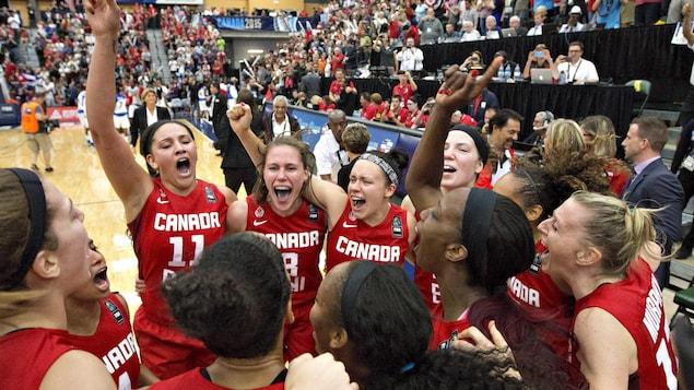 Regroupées devant le banc des joueuses et se tenant par les épaules, les membres de l'équipe canadienne de basketball féminin célèbrent leur qualification olympique.