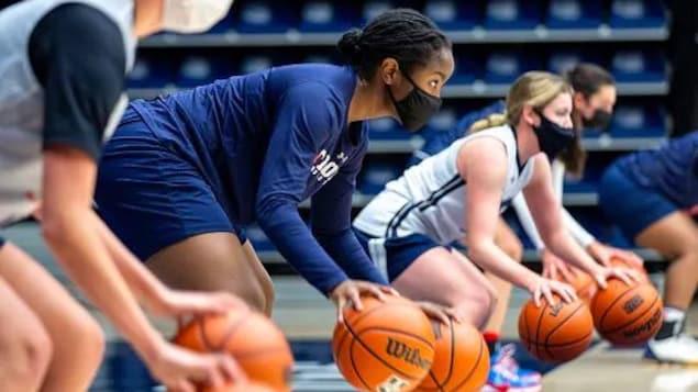 Des joueuses de basketball dribblent avec des ballons sur les lignes de côté d'un terrain.