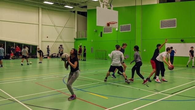 Des adolescents jouent au basketball et au soccer dans un gymnase.