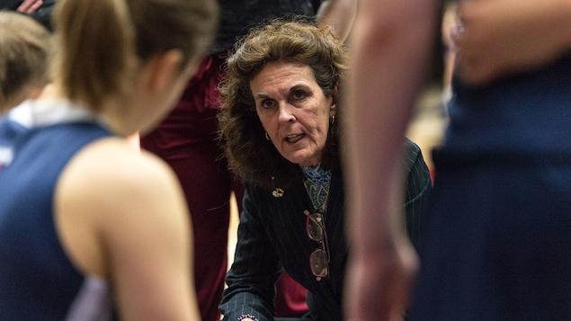 Une entraîneuse donne des directives aux joueuses de son équipe de basketball universitaire.