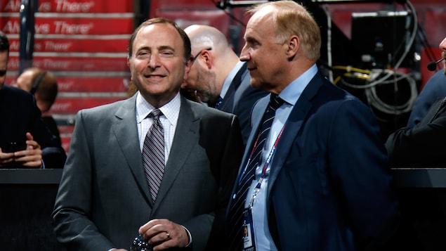 Deux hommes en complet discutent pendant une séance de repêchage.