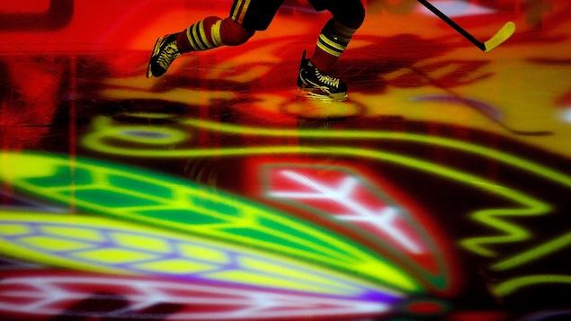 Un joueur des Blackhawks s'échauffe alors que le logo de l'équipe est projeté sur la glace.