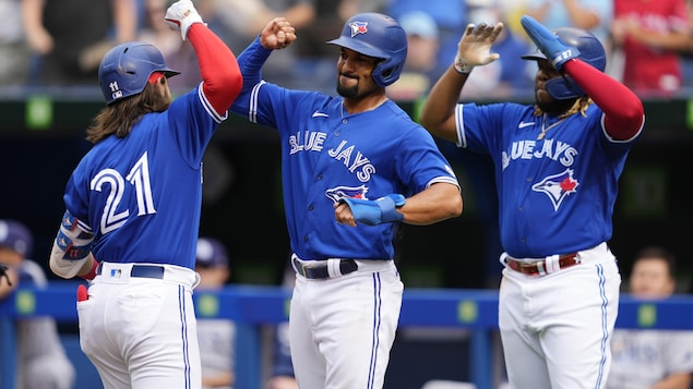 Trois joueurs de baseball se tapent dans les mains.
