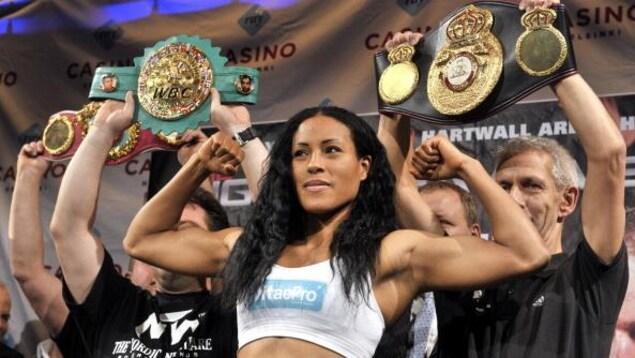 La boxeuse montre ses muscles en conférence de presse.