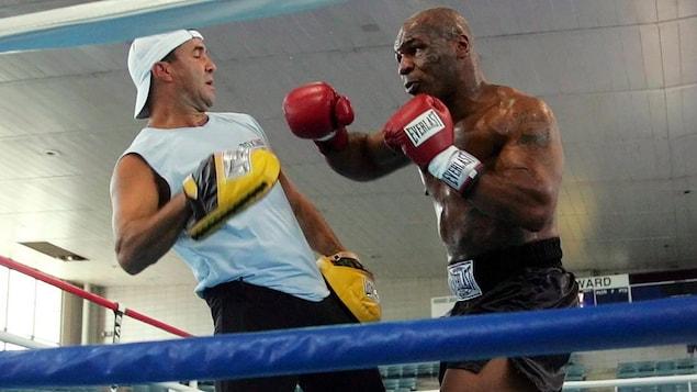 Un boxeur s'élance vers son partenaire d'entraînement.