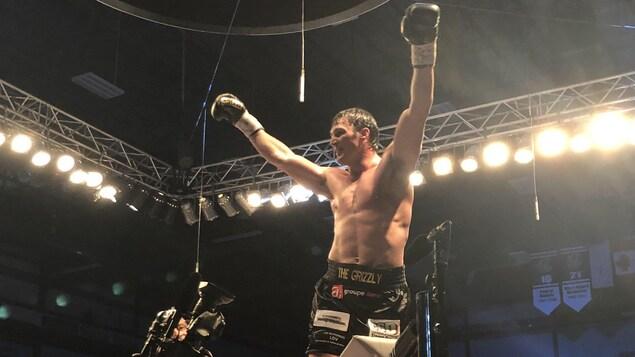 Il lève les bras au ciel pour célébrer sa victoire contre Dillon Carman.