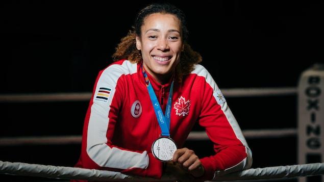 La boxeuse, tout sourire, s'appuie sur le plus haut câble du ring.