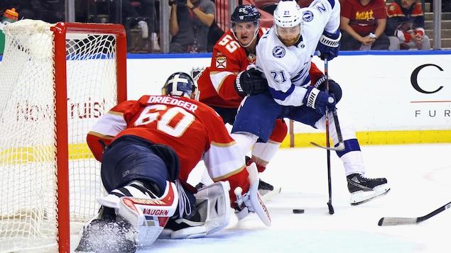 L'attaquant du Lightining, suivi de près par Noel Acciari, essaie de contrôler la rondelle entre ses patins devant le filet de Chris Driedger. Le gardien des Panthers tente de harponner le disque.