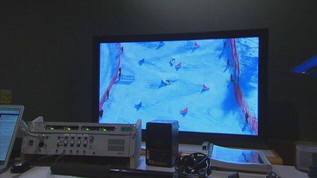 Une épreuve de surf des neiges est présentée sur un petit écran de télévision qui est utilisé par les descripteurs de Radio-Canada