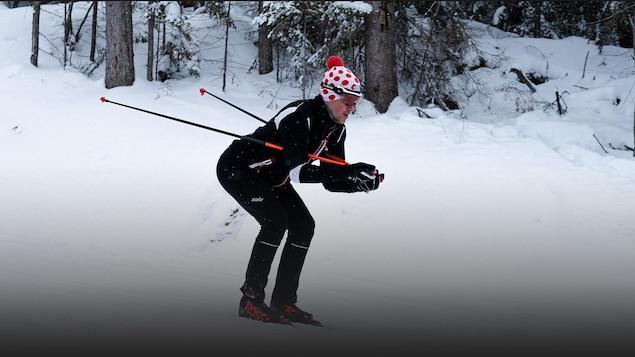 Photo d'un skieur de fond descendant une pente en forêt.