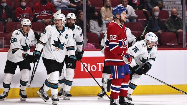 Les joueurs des Sharks s'apprêtent à patiner vers leur banc après un but, tandis que Jonathan Drouin regarde au loin, l'air dépité.