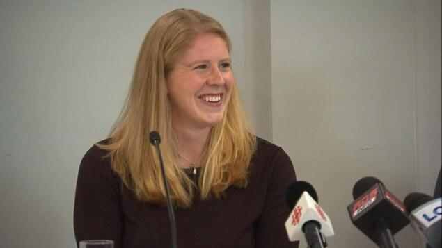 Elle sourit après avoir répondu à une question.