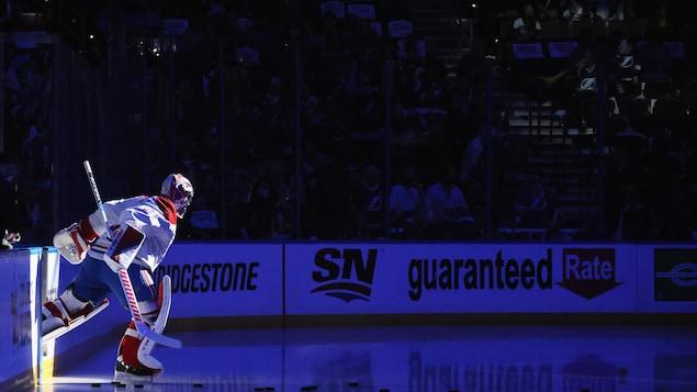 Le gardien but de hockey saute sur la glace, dans la pénombre, avec le projecteur sur lui.