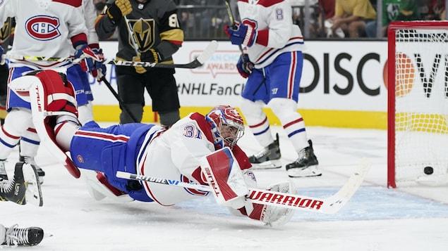 Le gardien du Canadien est en plein vol, plonge pour essayer d'arrêter un tir à sa droite, mais la rondelle est derrière lui, dans le filet.