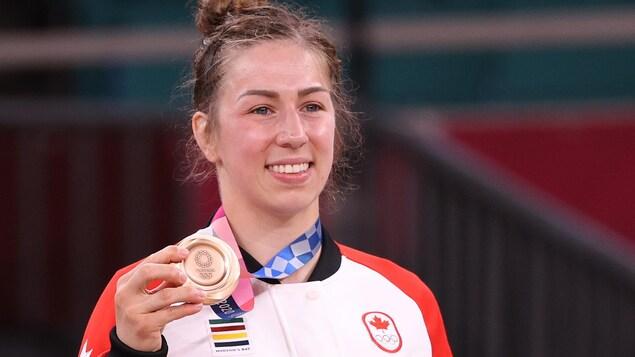 Souriante, elle tient de la main droite sa médaille de bronze.