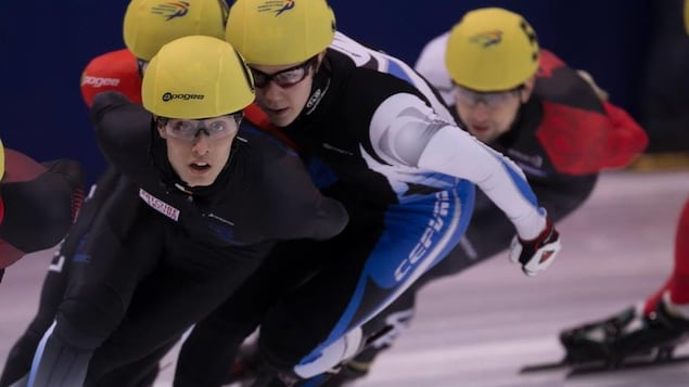 Il patine dans un peloton avec d'autres athlètes.