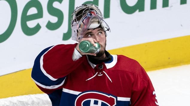 Le masque sur la tête, il boit une gorgée d'eau lors d'un arrêt de jeu.