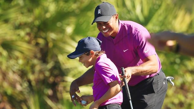 Un père et son fils jouent au golf.