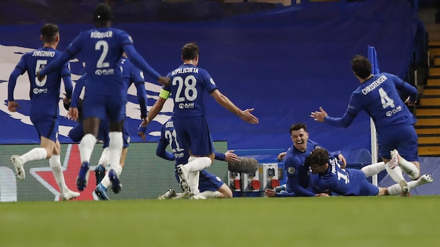 Mason Mount, allongé au sol, célèbre son but, le deuxième de Chelsea, entouré par ses coéquipiers.