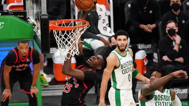 Il saute vers le panier pour réaliser un dunk, surveillé par un joueur des Celtics.