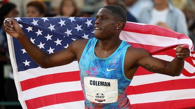Il tient un drapeau américain derrière son dos.