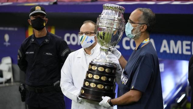 Des travailleurs de la santé du Brésil, portant le masque, posent pour une photo avec le trophée de la Copa América avant un match à Brasilia.