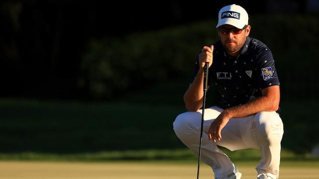 Corey Conners, accroupi, regarde le terrain de golf.
