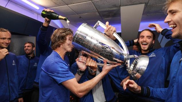 Des hommes boivent du champagne à même une immense coupe en métal.