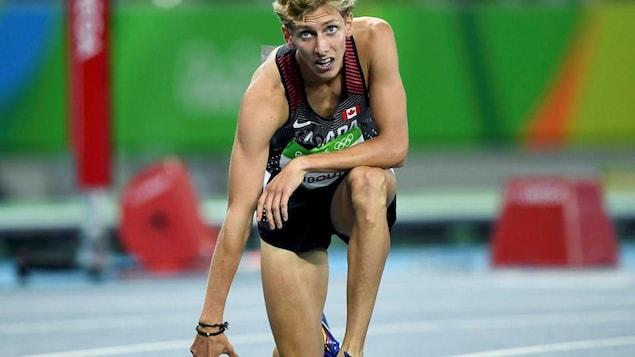 Le coureur de fond québécois s'agenouille sur la piste d'athlétisme aux Jeux olympiques de Rio en 2016.