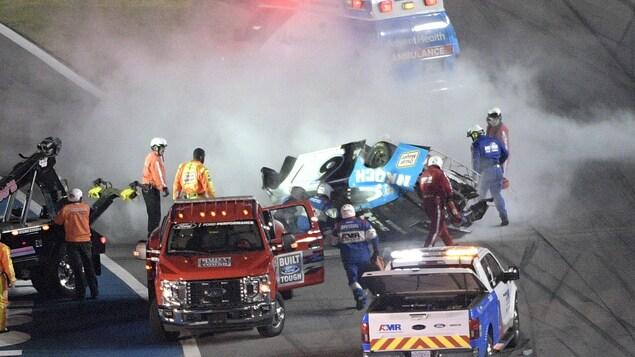 Le personnel de course s'approche de la voiture.