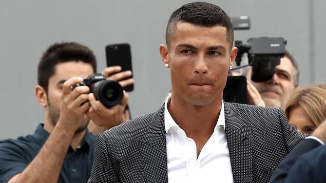 Il est photographié dans une salle de cour.