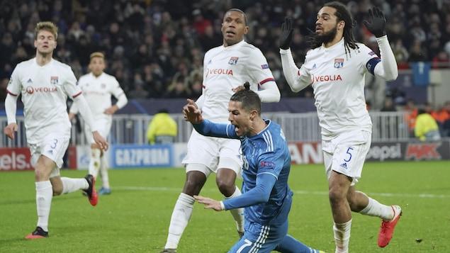 Cristiano Ronaldo chute dans la surface de réparation devant deux joueurs de Lyon.