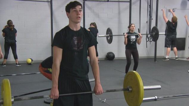 Plusieurs élèves soulèvent des poids pendant que leurs collègues effectuent d'autres exercices.