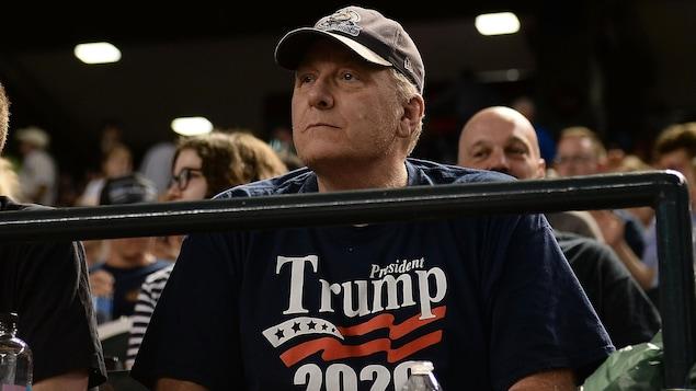Un homme avec un chandail bleu soutenant Donald Trump dans les gradins.