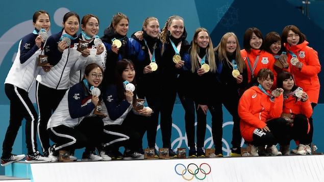 L'équipe coréenne de curling (à gauche), médaillée d'argent, sur le podium des Jeux olympiques de 2018