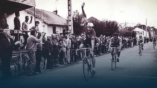 Le cycliste Dany Deslongchamps lève un bras en croisant la ligne d'arrivée d'une course.