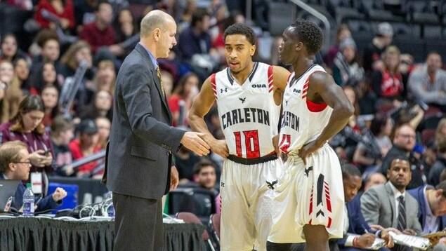 Un entraîneur s'adresse à deux joueurs sur un terrain de basketball