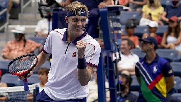 Un joueur de tennis vêtu d'un chandail blanc et d'un bandeau bleu sur le front lève le poing après une victoire