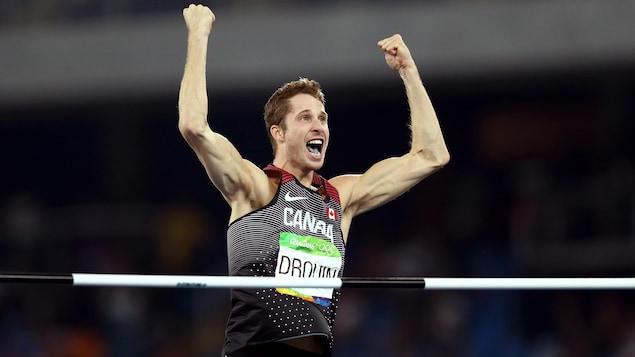 Il lève les bras pendant une compétition.