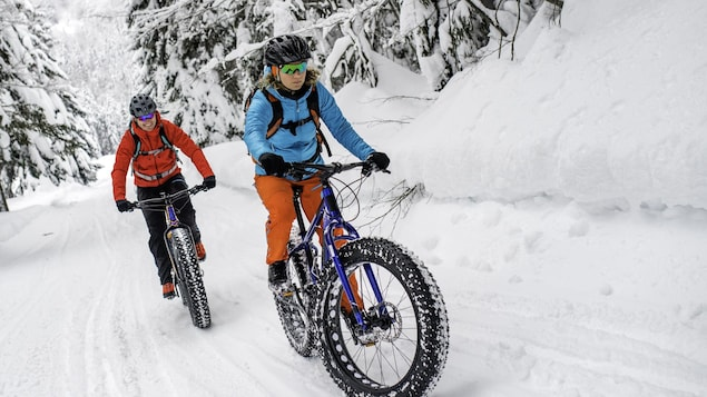 Deux cyclistes dans un sentier de neige