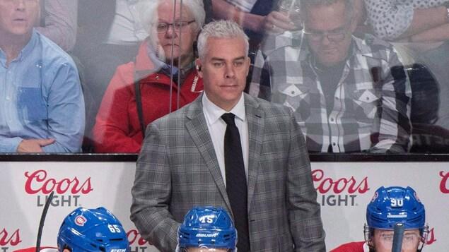 Un entraîneur de hockey debout derrière le banc des joueurs.