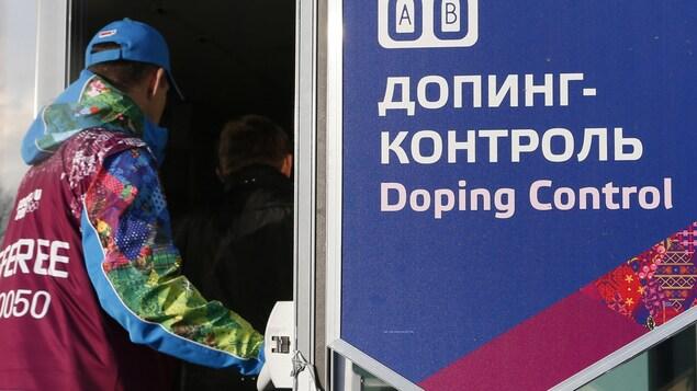 Un employé entre dans le centre anti-dopage au stade biathlon et centre Laura Cross Country aux Jeux olympiques d'hiver de Sochi en 2014.