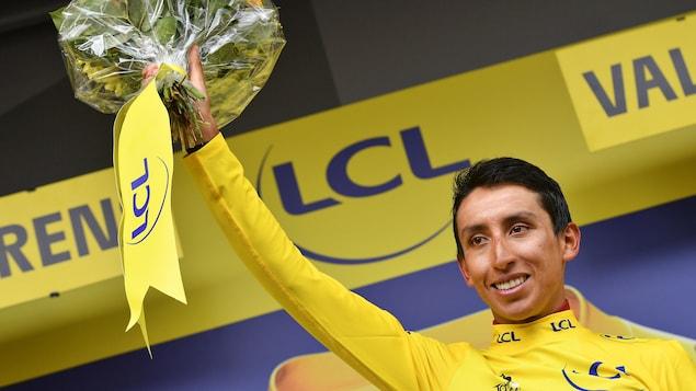 Il endosse le maillot jaune sur le podium et tient à bout de bras un bouquet de fleurs.