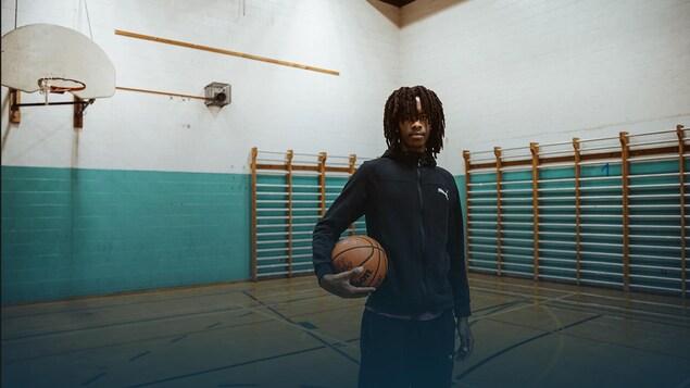 Elie Karojo se tient de bout sur un terrain de basketball en tenant un ballon.