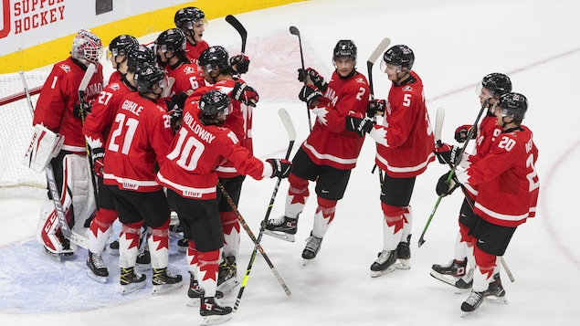 Les joueurs de l'équipe canadienne de hockey junior célèbrent leur victoire.