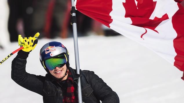 Il lève un bras avec le drapeau canadien sur son épaule.